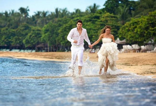 newlyweds running along the beach